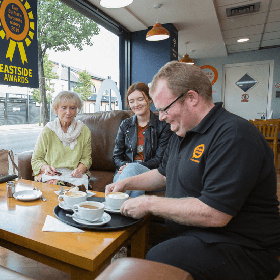 man serving customers at the Orchardville Café in Belfast