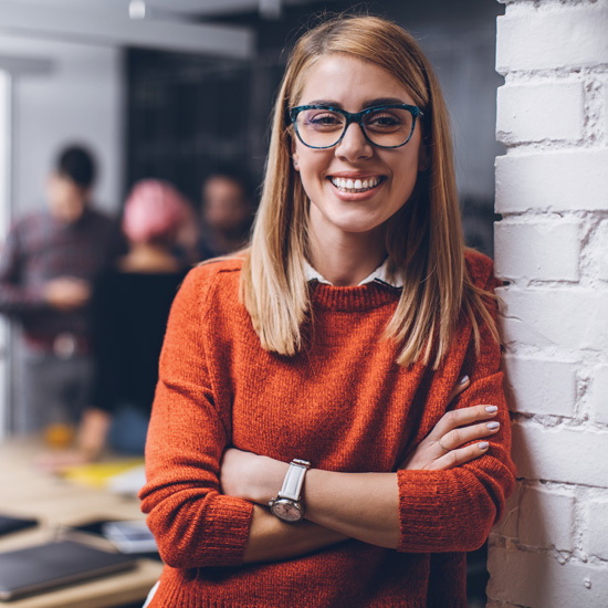 woman in glasses leaning against a wall and smiling